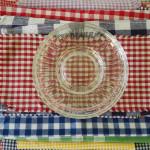"""""""by your table"""", detalj av installasjon, samling av tekstiler og glassfat"""